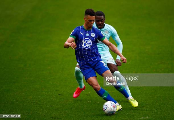 Antonee Robinson of Wigan Athletic and Bright OsayiSamuel of Queens Park Rangers battle for the ball during the Sky Bet Championship match between...