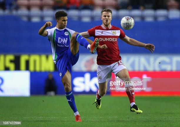 Antonee Robinson of Wigan Athletic clears the ball under pressure from Marley Watkins of Bristol City during the Sky Bet Championship match between...