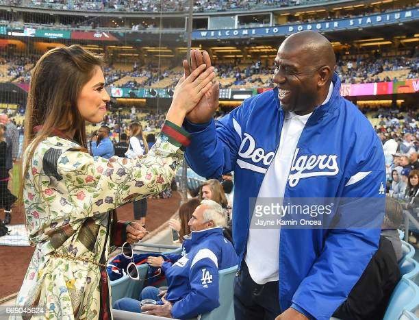 Antonella Barba gets a high five from Magic Johnson after singing the National Anthem before the game between the Los Angeles Dodgers and the Arizona...
