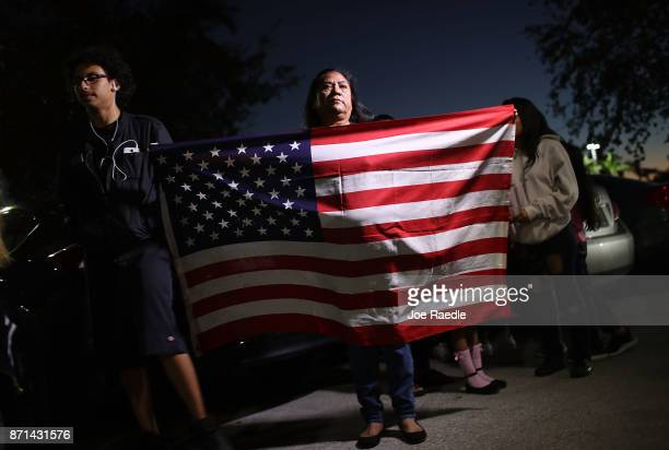 Antonia Catalon originally from Mexico and now living in the US for 30 years holds an American flag as she joins with others in front of the offices...