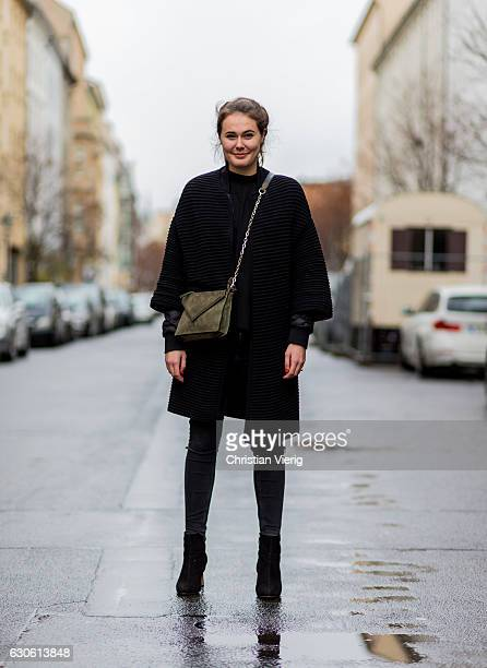 Antonia Petrioli wearing a black jacket dark grey denim skinny jeans a green olive bag black heeled ankle boots on December 28 2016 in Berlin Germany