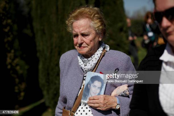 Antonia Santiago Garcia walks during a memorial at the Forest of the Absent as she holds a picture of her daughter Maria Dolores Duran Santiago who...