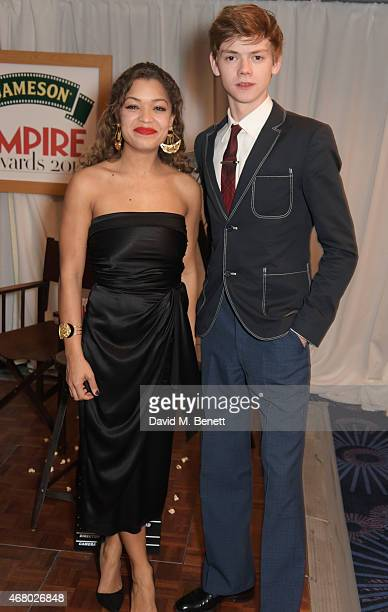 Antonia Thomas and Thomas BrodieSangster pose in the Winners Room after presenting an award at the Jameson Empire Awards 2015 at Grosvenor House on...