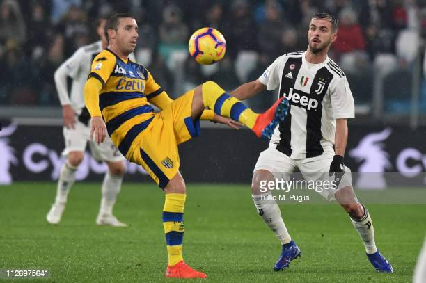 Antonino Barilla of Parma competes for the ball with Miralem Pjanic of Juventus during the Serie A match between Juventus and Parma Calcio at Allianz...