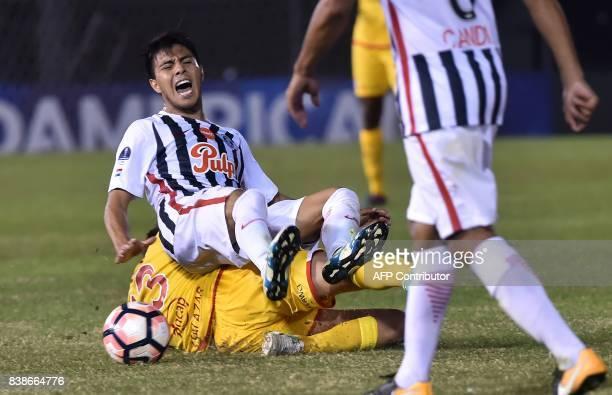 Antonio Bareiro of Paraguay's Libertad falls over Sebastian Salazar of Colombia's Independiente Santa Fe during their Copa Sudamericana football...