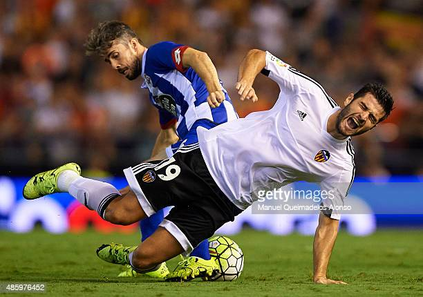 Antonio Barragan of Valencia is tackled by Luisinho Correia of Deportivo during the La Liga match between Valencia CF and RC Deportivo de La Coruna...