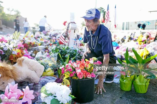 Antonio Basco, who's wife Margie Reckard was one of 22 persons killed by a gunman at a local Walmart, lays flowers in her honor at a makeshift...