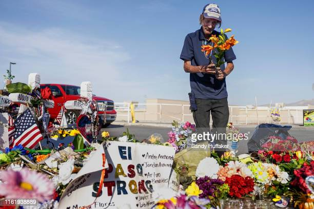 Antonio Basco who's wife Margie Reckard was one of 22 persons killed by a gunman at a local Walmart lays flowers in her honor at a makeshift memorial...