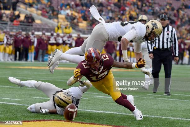 Antonio Blackmon and Brennan Thieneman of the Purdue Boilermakers break up a touchdown pass intended for Rashod Bateman of the Minnesota Golden...
