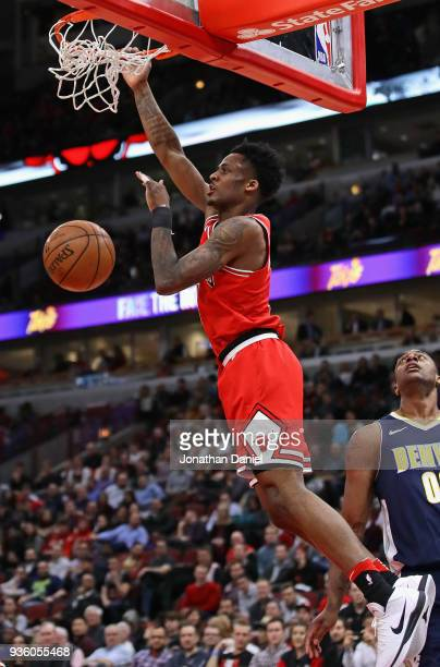 Antonio Blakeney of the Chicago Bulls dunks over Darrell Arthur of the Denver Nuggets at the United Center on March 21 2018 in Chicago Illinois The...