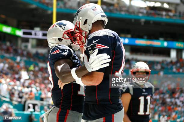 Antonio Brown of the New England Patriots celebrates with Tom Brady after scoring a touchdown against the Miami Dolphins during the second quarter in...