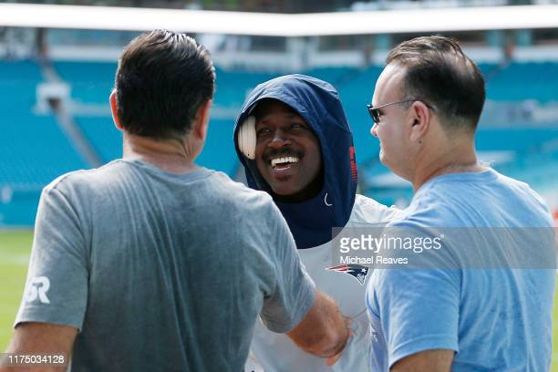 Antonio Brown of the New England Patriots laughs with agents Drew and Jason Rosenhaus prior to the game between the Miami Dolphins and the New...
