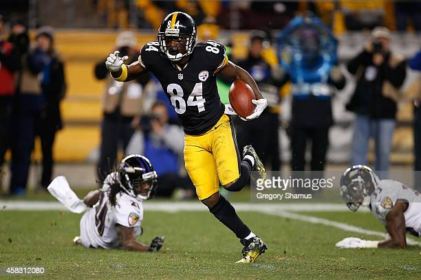 Antonio Brown of the Pittsburgh Steelers avoids a tackle by Lardarius Webb and Will Hill of the Baltimore Ravens and scores a 54 yard touchdown...