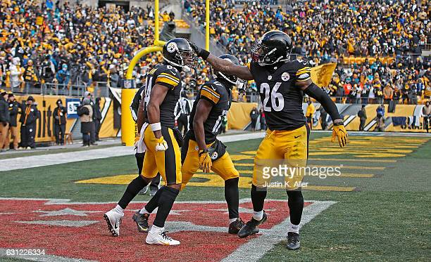 Antonio Brown of the Pittsburgh Steelers celebrates his touchdown with Le'Veon Bell and Eli Rogers in the first quarter during the Wild Card Playoff...