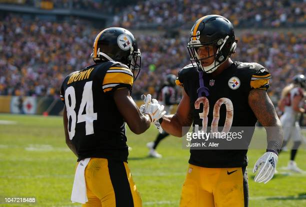 Antonio Brown of the Pittsburgh Steelers celebrates with James Conner after a 9 yard touchdown reception in the second half during the game against...