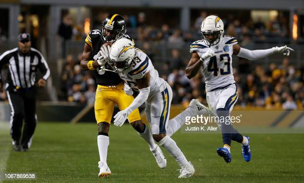 Antonio Brown of the Pittsburgh Steelers is hit after a catch by Derwin James of the Los Angeles Chargers in the first half during the game at Heinz...