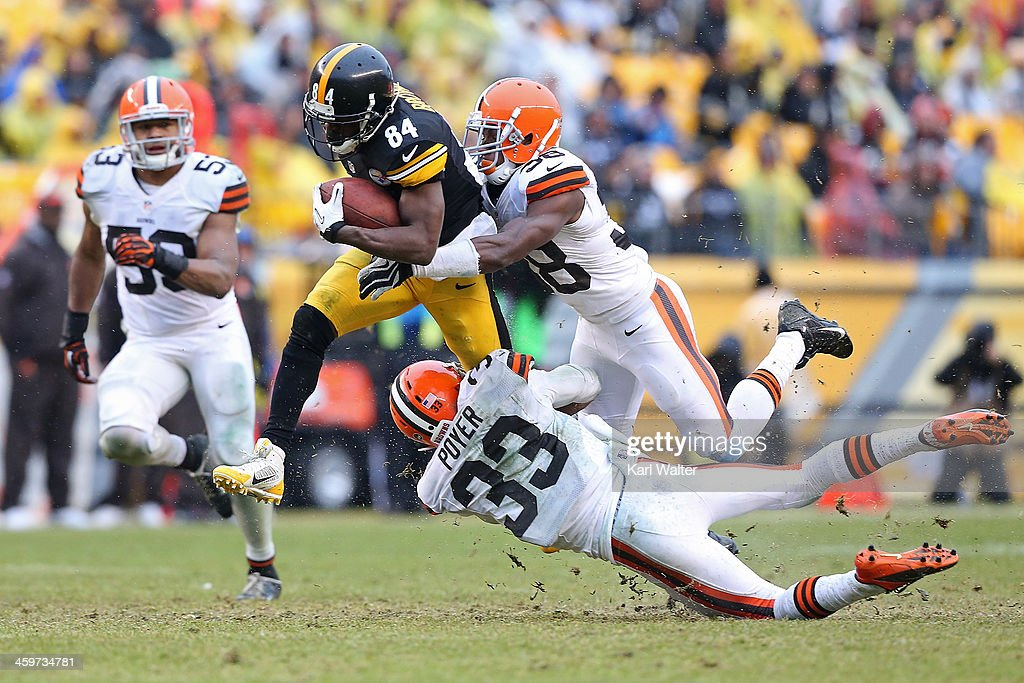 Antonio Brown #84 of the Pittsburgh Steelers is tackled by #33 Jordan Poyer and #38 Julian Posey of the Cleveland Browns during the game at Heinz Field on December 29, 2013 in Pittsburgh, Pennsylvania. The Steelers defeated the Browns 20-7.