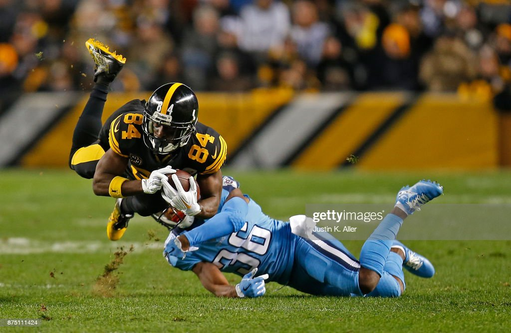 Antonio Brown #84 of the Pittsburgh Steelers is tripped up for a tackle by LeShaun Sims #36 of the Tennessee Titans in the first quarter during the game at Heinz Field on November 16, 2017 in Pittsburgh, Pennsylvania.