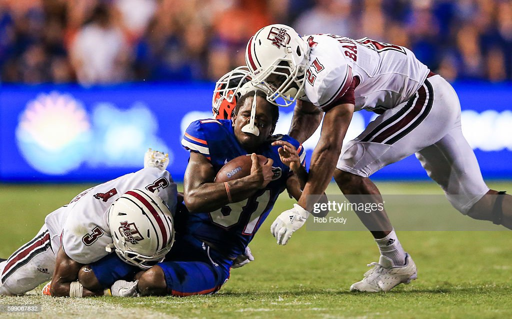 Antonio Callaway #81 of the Florida Gators has his helmet knocked off by Khary Bailey-Smith #21 and Lee Moses #3 of the Massachusetts Minutemen during the second half of the game at Ben Hill Griffin Stadium on September 3, 2016 in Gainesville, Florida.