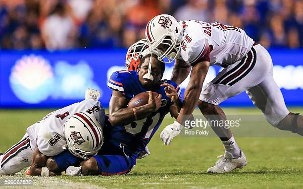 Antonio Callaway of the Florida Gators has his helmet knocked off by Khary BaileySmith and Lee Moses of the Massachusetts Minutemen during the second...