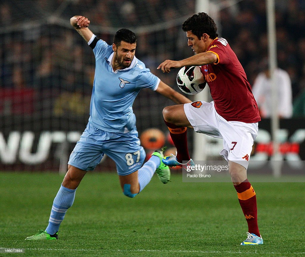 Antonio Candreva (L) of S.S. Lazio competes for the ball with Marquinho of AS Roma during the Serie A match between AS Roma and S.S. Lazio at Stadio Olimpico on April 8, 2013 in Rome, Italy.