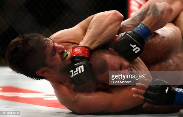 Antonio Carlos Junior of Brazil secures a rear choke submission against Eric Spicely in their middleweight bout during the UFC 212 event at Jeunesse...