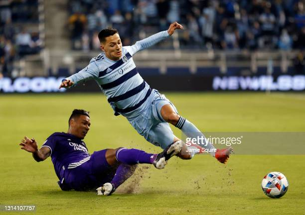 Antonio Carlos of Orlando City slide-tackles Daniel Salloi of Sporting Kansas City during the Major League Soccer game at Children's Mercy Park on...