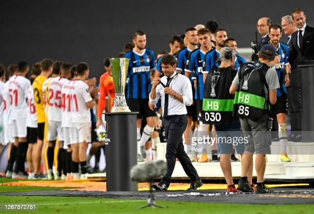 Antonio Conte Head Coach of Inter Milan walks past the UEFA Europa League Trophy with his runners up medal following his team's defeat in the UEFA...
