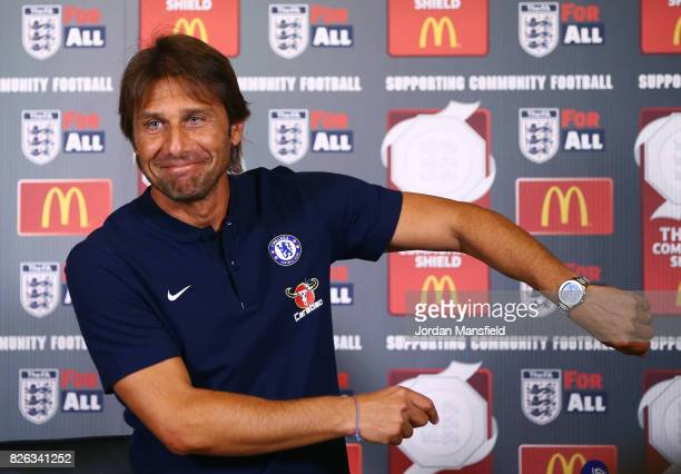 Antonio Conte manager of Chelsea gestures to his watch as he makes his way into a Chelsea Press Conference at Chelsea Training Ground on August 4...