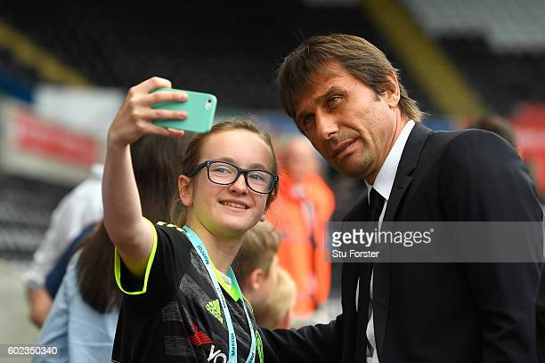 Antonio Conte manager of Chelsea poses for selfie photographs with fans prior during the Premier League match between Swansea City and Chelsea at...