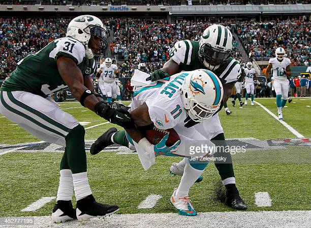 Antonio Cromartie and DeMario Davis of the New York Jets converge on Mike Wallace of the Miami Dolphins during their game at MetLife Stadium on...