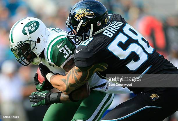 Antonio Cromartie of the New York Jets is tackled by Jason Babin of the Jacksonville Jaguars during the game at EverBank Field on December 9 2012 in...