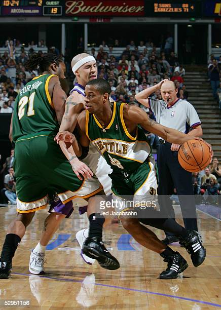 Antonio Daniels of the Seattle SuperSonics drives around a pick set by Danny Fortson on Mike Bibby of the Sacramento Kings in Game three of the...