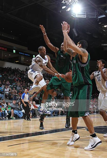 Antonio Daniels of the Texas Legends passes the ball between Marcus Cousin and Danny Green of the Austin Toros on April 2 2011 at the Cedar Park...