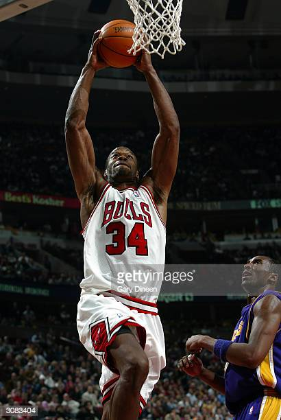 Antonio Davis of the Chicago Bulls dunks past Kobe Bryant of the Los Angeles Lakers during the fourth quarter March 13 2004 at the United Center in...