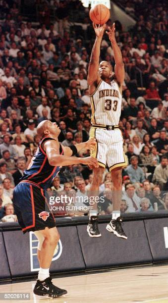 Antonio Davis of the Indiana Pacers shoots from long range 05 May as Terry Cummings of the New York Knicks stands and watches during the first half...