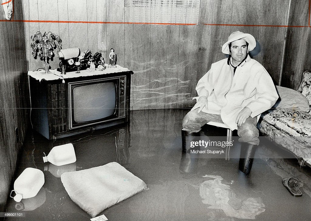 Antonio Fazzalari of Hullmar Dr. wears rubber boots as he inspects his flooded basement... : News Photo