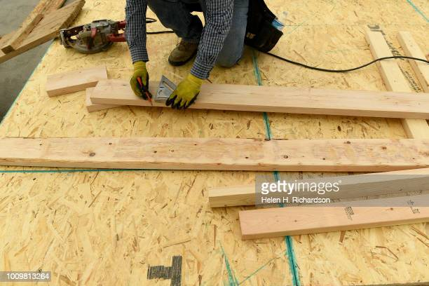 Antonio Flores measures pieces of wood to cut carries while working on a new home in the Beeler Park neighborhood of Stapleton on August 1 in Denver...