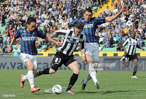 Antonio Floro Flores of Udinese is challenged to Yuto Nagatomo and Lucio of Internazionale Milano during the Serie A match between Udinese Calcio and...