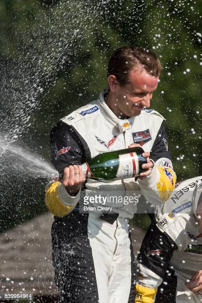 Antonio Garcia of Spain celebrates with champagne after winning the Michelin GT Challenge WeatherTech SportsCar Series race at Virginia International...