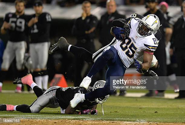 Antonio Gates of the San Diego Chargers gets tackled by Kevin Burnett of the Oakland Raiders during the fourth quarter at Oco Coliseum on October 6...