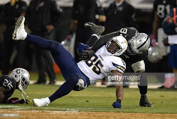 Antonio Gates of the San Diego Chargers is tackled by Kevin Burnett of the Oakland Raiders during the fourth quarter at Oco Coliseum on October 6...