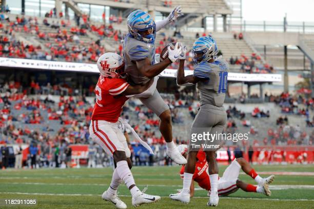 Antonio Gibson of the Memphis Tigers leaps over Gervarrius Owens of the Houston Cougars for a touchdown in the third quarter at TDECU Stadium on...