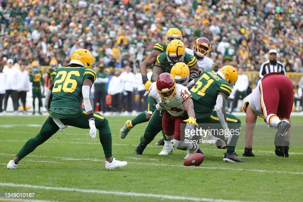 Antonio Gibson of the Washington Football Team fumbles a ball during a game against the Green Bay Packers at Lambeau Field on October 24, 2021 in...