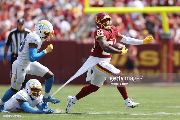 Antonio Gibson of the Washington Football Team runs with the ball away from Kyzir White of the Los Angeles Chargers during the first quarter at...
