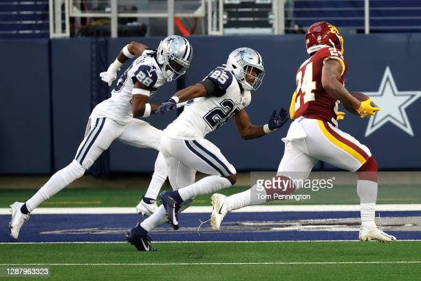 Antonio Gibson of the Washington Football Team rushes for a five yard touchdown ahead of defenders Xavier Woods and Rashard Robinson of the Dallas...