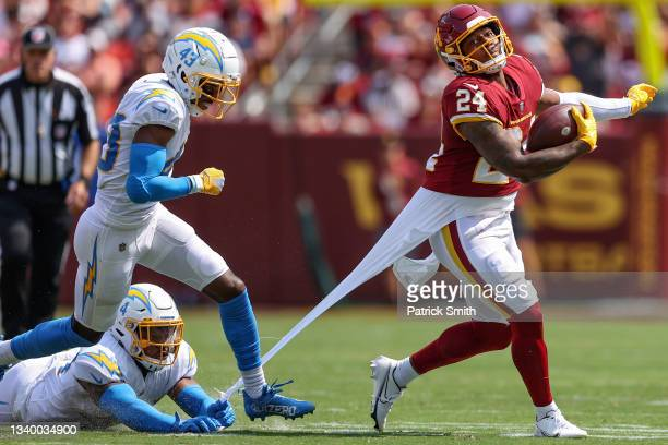 Antonio Gibson of the Washington Football Team rushes past Michael Davis and Kyzir White of the Los Angeles Chargers during the first quarter at...