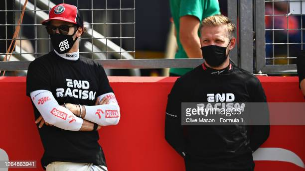 Antonio Giovinazzi of Italy and Alfa Romeo Racing and Kevin Magnussen of Denmark and Haas F1 stand on the grid before the F1 70th Anniversary Grand...