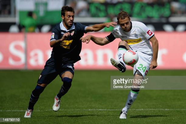Antonio Luna of Sevilla challenges Tony Jantschke of Moenchengladbach during the friendly match between Borussia Moenchengladbach and FC Sevilla at...