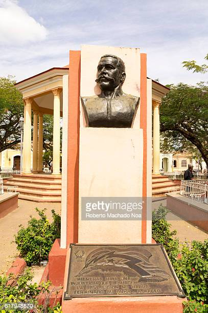 Antonio Maceo bronze statue in Remedios plaza Memorial with a bust on a wall in a garden